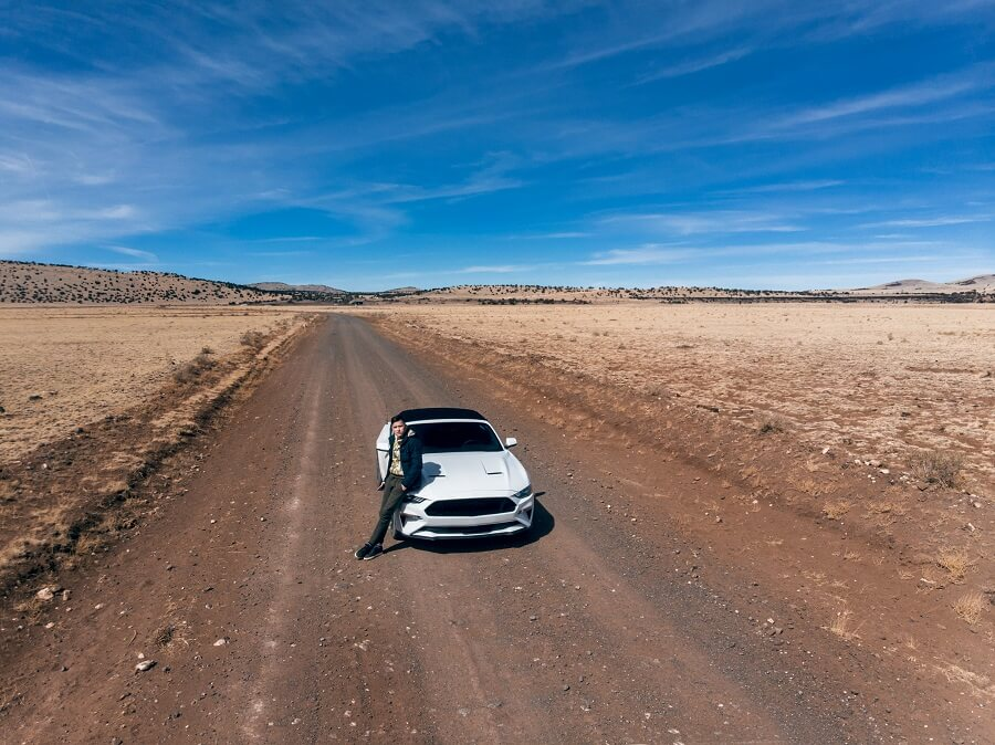 Man Traveling By Car On The Desert Road