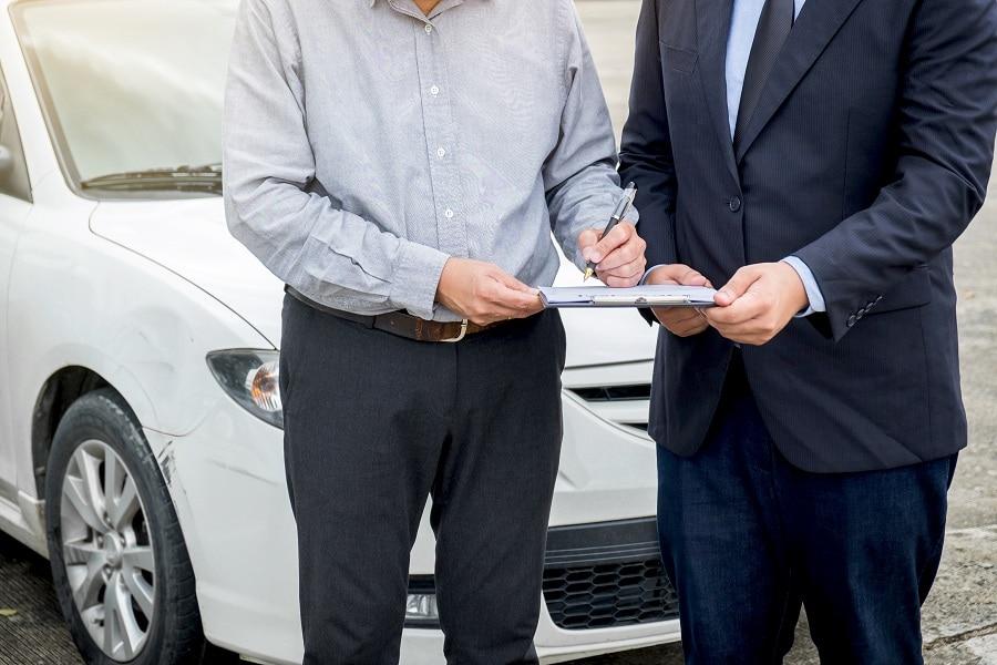 Insurance Agent Examine Damaged Car And Customer Filing Signature